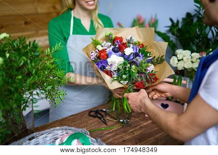 Seller of flowers giving arranged bouquet to buyer