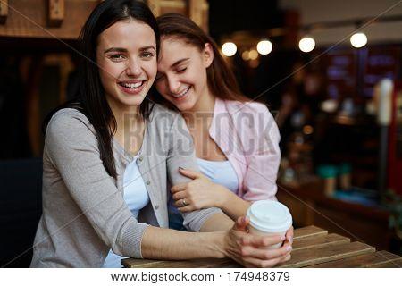 Ecstatic girls having drinks in cafe