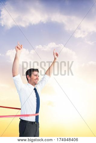 Composite image of a businessman winning the race against sky in the background