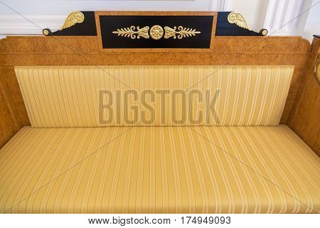 Striped yellow-brown retro sofa with gold inserts