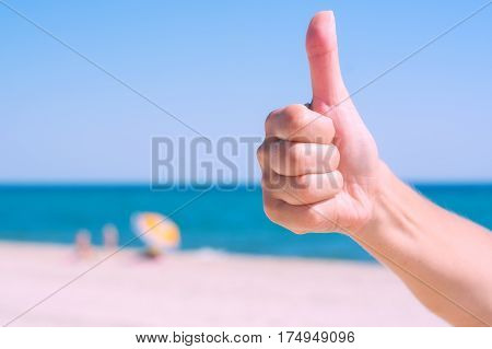 Woman's hand showing thumbs up or shows good and like on the beach against blue sea background.