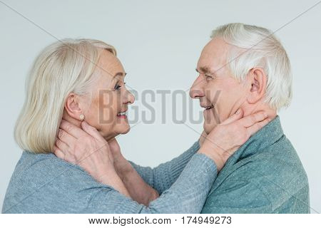 side view of smiling senior couple looking at each other on white