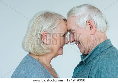 side view of senior man and woman looking at each other on grey