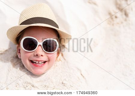Adorable little girl at beach having fun buried in the sand during summer vacation