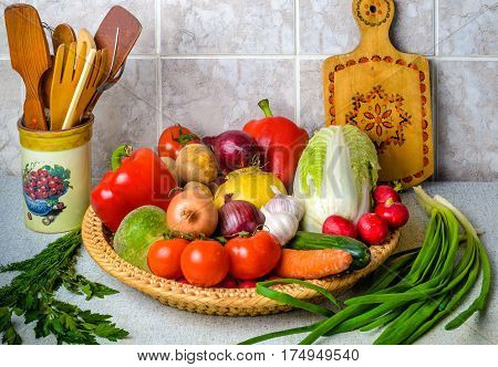 On the kitchen table in the large wicker basket are a variety of vegetables. Next in ceramic vase - wooden spoons and cutting Board.