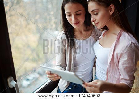 Teenage buddies reading online data in touchpad