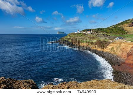 Wide angle view of volcanic coast, lighthouse and goat island in Terceira, Portugal