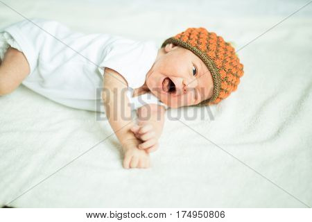 cute newborn baby beanie lying on the bed.the photo has a empty space for your text