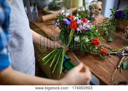 Woman tying up multi-floral bouquet