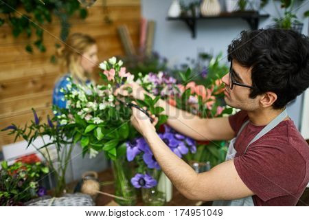 Young man cutting dry leaves while arranging floral bouquets
