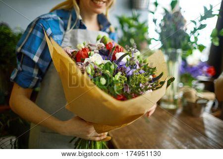 Vendor of flowers holding arranged bouquet