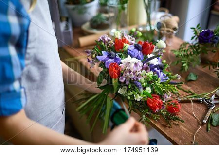Female tying up bunch of fresh flowers