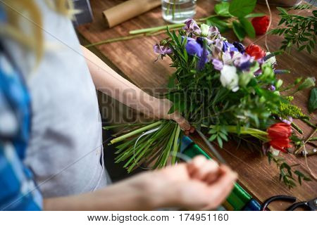 Florist tying floral bouquet with ribbon