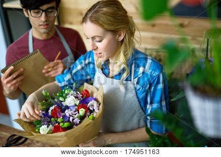 Young woman aranging bouquet with her colleague near by