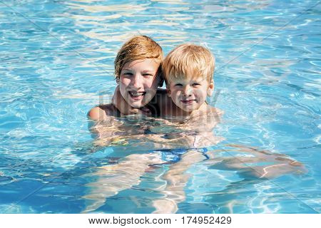 Two smiling brothers in the pool.Boys have a good time in aquapark in the summer
