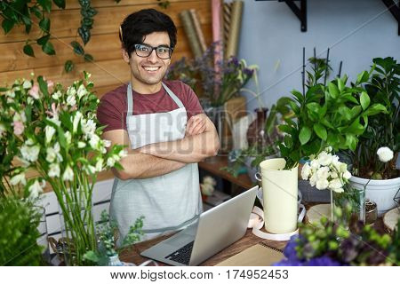 Young vendor of flowers standing by counter in flower-shop