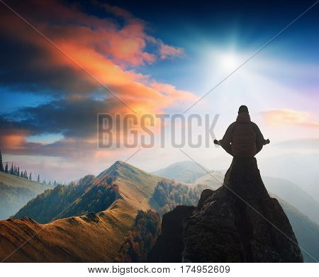 Silhouette of human meditating in sitting yoga position on the top of a mountain in a foggy valley. Zen meditation peace