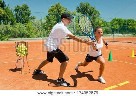 Tennis coach working with female student explaining volley