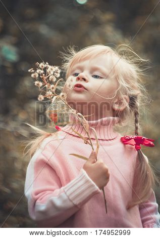 Little blonde girl blowing dandelion autumn close-up