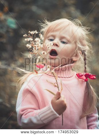 Little blonde girl blowing dandelion autumn close-up open mouth