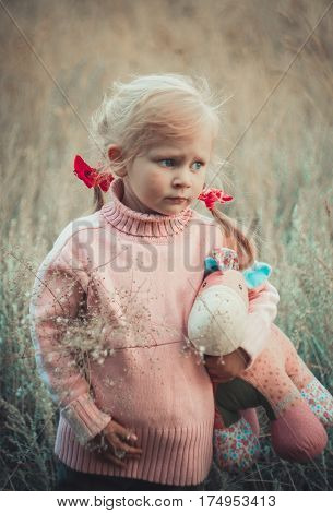 Adorable sad girl with hourse toy in park autom