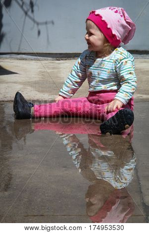 little girl playing with water in puddle