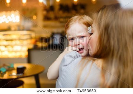 Girl in tears looking at camera while mother kissing her