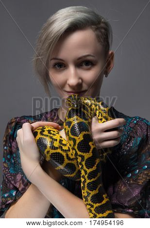 Young woman holding yellow anaconda on gray background