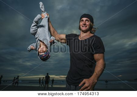 Athletic father with lovely newborn daughter over sea and sunset background.  Father is doing with baby dynamic gymnastics