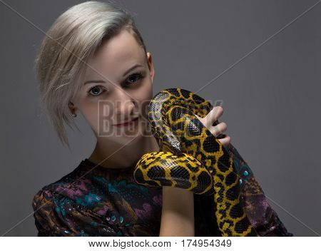 Blond smiling woman holding anaconda on gray background