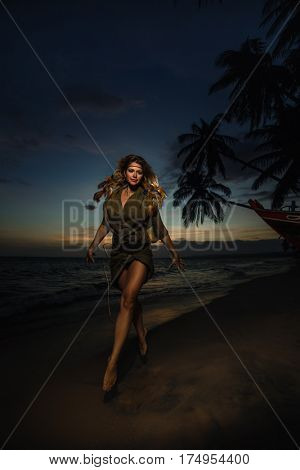 Portrait of woman with feathers in hair in tribal costume next to boat against sunset