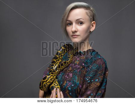 Blond woman and yellow anaconda on gray background