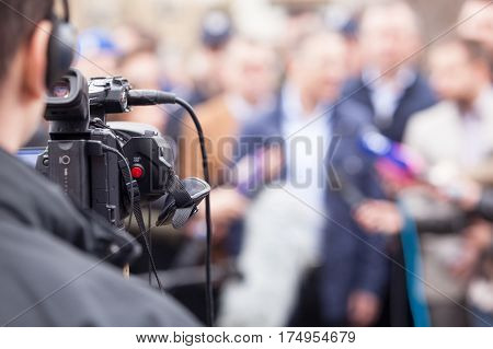 Filming an event with a television camera. News conference.