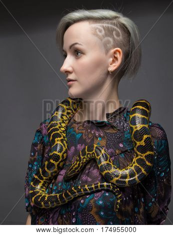 Blond woman and yellow reptile on gray background