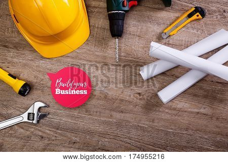 Yellow helmet, drill and flashlight. Build your business speech bubble. Construction concept. Adjustable wrench, architecture plans and knifes.