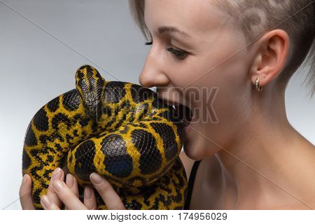 Woman biting yellow snake on gray background