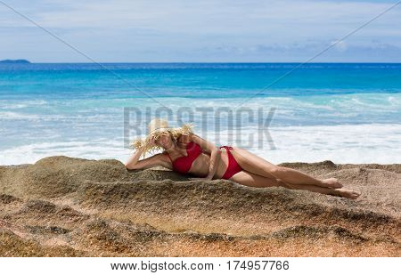 Beautiful woman in straw sun hat and red swimsuit, Seychelles