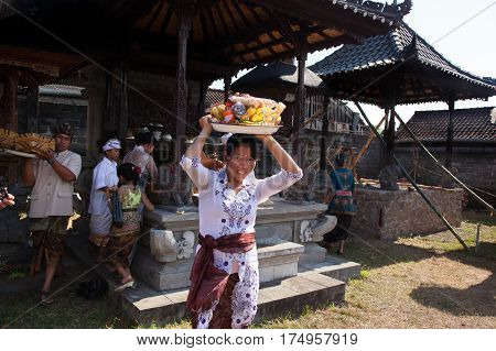 BALI INDONESIA - AUGUST 28 2012: A man and a woman carried gifts for the religious ceremony Galungan