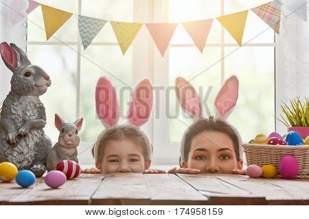 Happy easter! Mother and daughter begin to hunt for Easter eggs. Happy family preparing for Easter. Cute little child girl wearing bunny ears on Easter day.