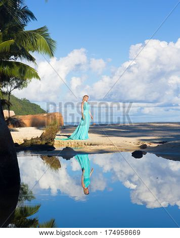 Blonde woman in turquoise long dress at the beach, Seychelles