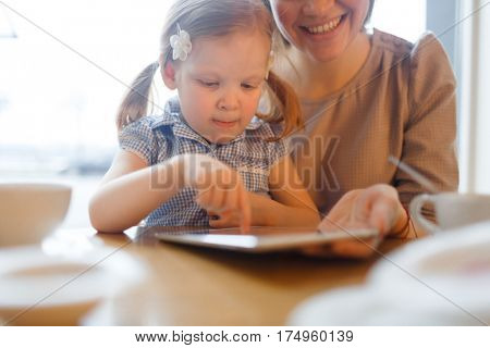 Curious girl browsing in the net while her mother holding touchpad