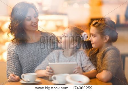 Woman and her daughters addicted to gadgets spending time with touchpad in cafe
