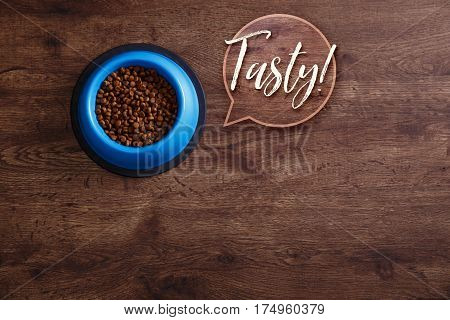 Bowl of dry kibble dog food. Tasty speech bubble. Healthy pets feed. Blue plate on wooden rustic background.