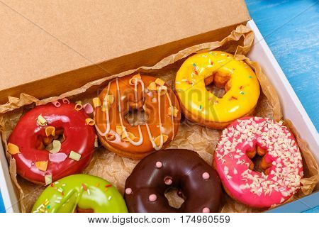 Donuts with icing. Sweet glazed donut. Dessert with sprinkles in delivery box. On blue wooden rustic background.