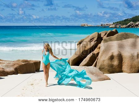 Pretty woman in turquoise blue swimsuit, at dream beach, Seychelles