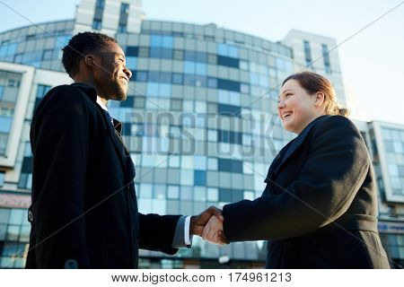 Portrait of two international business partners shaking hands against office building outdoors. African-American man and young Caucasian woman.