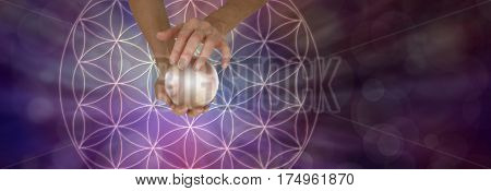Sacred Geometry and Crystal Ball Scrying - Female holding a large crystal ball above a Flower of Life Symbol on a wide purple bokeh background with copy space