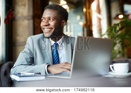 Portrait of handsome African- American businessman wearing formal suit looking away smiling joyfully while busy working with laptop in cafe