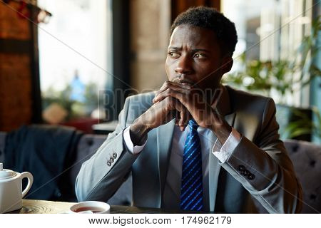 Portrait of handsome African American man wearing business suit looking away to window, pensive and worried while sitting at table in modern restaurant during coffee break