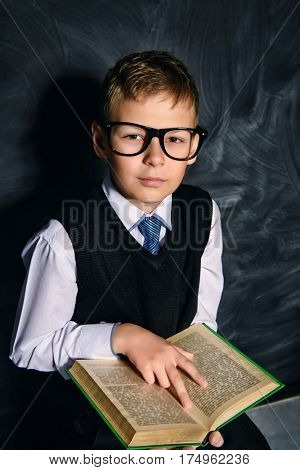 A schoolboy in elegant suit sitting by a blackboard with book. Educational concept. Copy space.